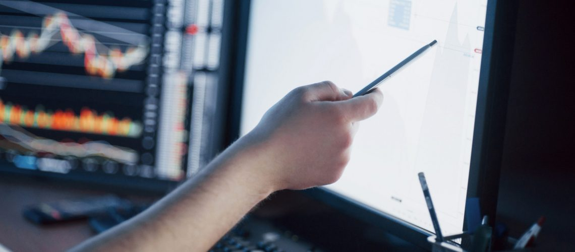 Analyzing data. Close-up of young businessman pointing on the data presented in the chart with pen while working in creative office.